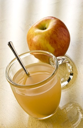 slings: Slings Apple Toddy in a cup with a spoon and an apple in the background