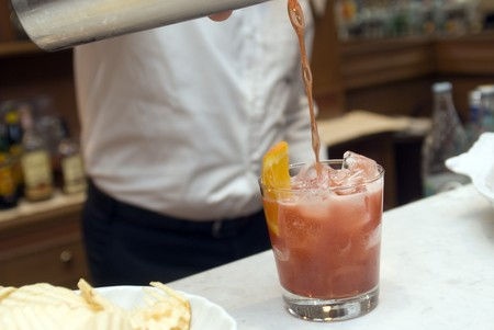 soporific: Barkeeper spills drink from shaker into glass Stock Photo