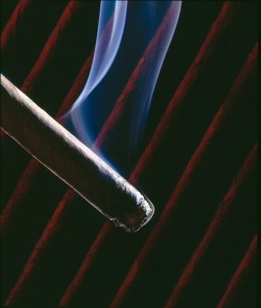 cigare: Light up a cigare, with smoke and moody background. Stock Photo