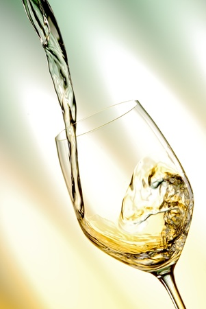Pour white vine into glass with light background. photo