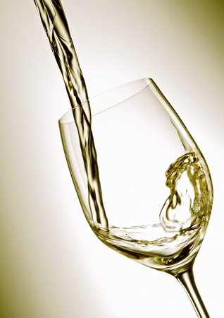 Pour white vine into glass with light background. Stock Photo - 8288458