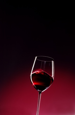 glass of red wine in a red and black background photo