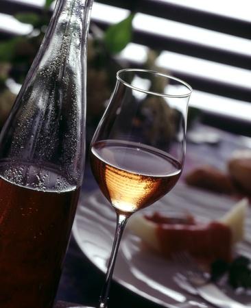 vetro e una bottiglia di vino ros? e cibo in background Archivio Fotografico