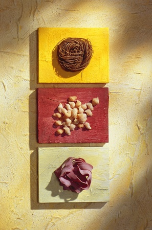 three sorts of pasta on boards in a yellow atmosphere photo