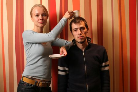 Young . Beautiful woman using her husband as a coffee coaster. photo