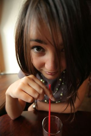 wide angle: Anime-style girl drinking juice or cocktail through red straw. Wide angle portrait. Stock Photo