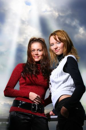 Two girlfriends, sky with rays of light shining trough dramatic clouds  behind them. photo