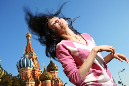 euforia: Young girl in euphoria waves her long hair over blue sky at Red Square, Moscow, Russia. Saint Basil's Cathedral behind.  Foto de archivo