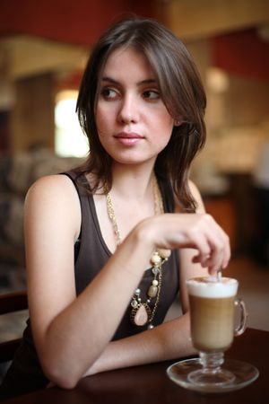 Beautiful young woman enjoying latte coffee in cafe. Shallow DOF. photo
