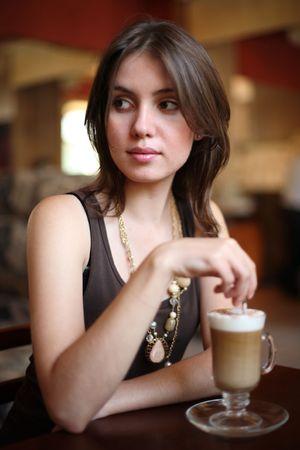 shallow dof: Beautiful young woman enjoying latte coffee in cafe. Shallow DOF.