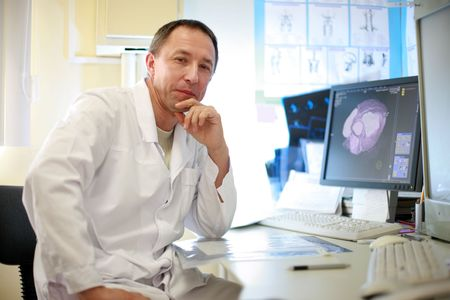 radiologist: A portrait of doctor sitting with CAT scan on the monitor and x-ray films on the table . Stock Photo