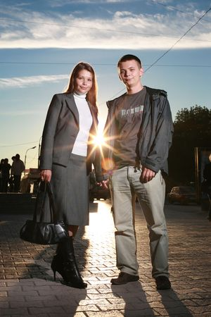 Portrait of a young couple standing on a street holding hands at sunset.