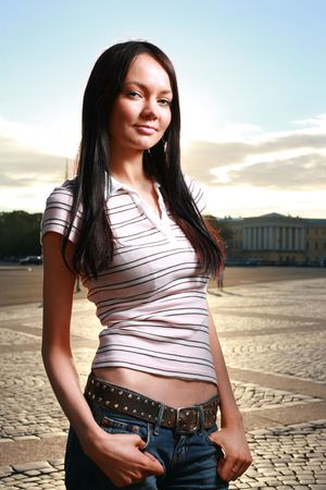 Beautiful young woman standing with hands in pockets photo