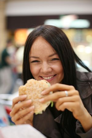 Beautiful girl eating hamburger and laughing. Shallow DOF. photo