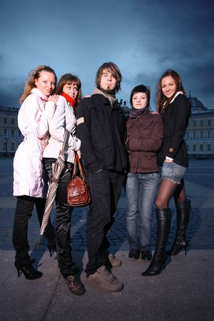 Group of five trendy young people standing in a city square photo