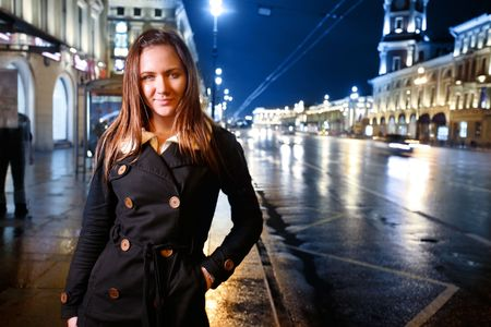Beautiful young woman standing on illuminated street at night. photo