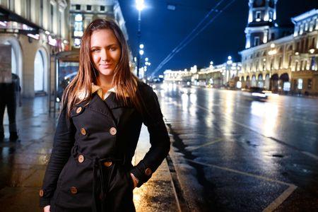 tonight: Beautiful young woman standing on illuminated street at night. Stock Photo