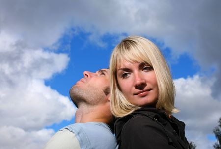 Man resting head on womans shoulder, looking at the sky. photo