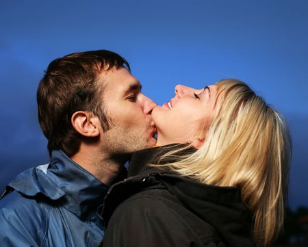 Young couple kissing outdoors at dusk. photo