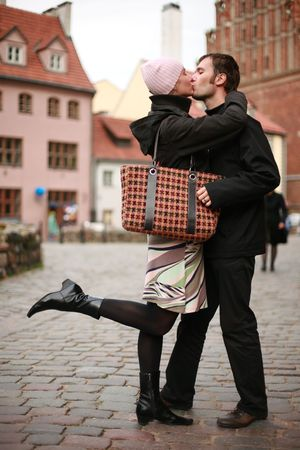 Young couple kissing in an old European town square.