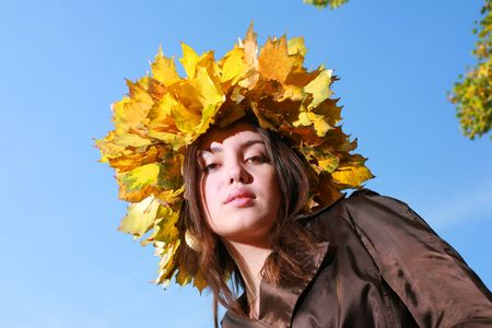 Beautiful young woman in crown of golden autumn leaves, blue sky behind. photo