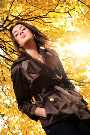 Beautiful young under tree branches with yellow autumn foliage in park, blowing a kiss. photo