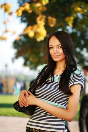 Beautiful young woman with purse on shoulder outdoors in park Stock Photo - 2458707