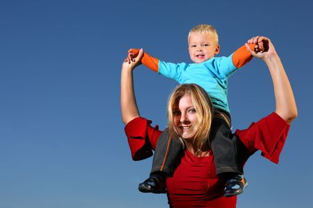 shoulder ride: Young boy riding on his mothers shoulders, outdoors , blue sky behind. Stock Photo