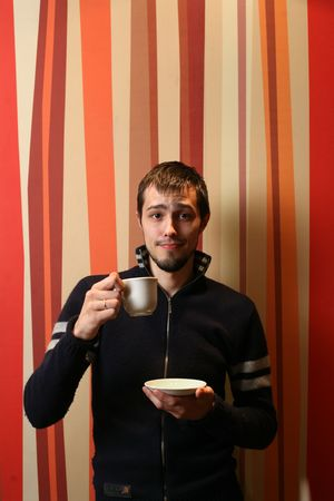 Cool young man with cup of tea or coffee. photo