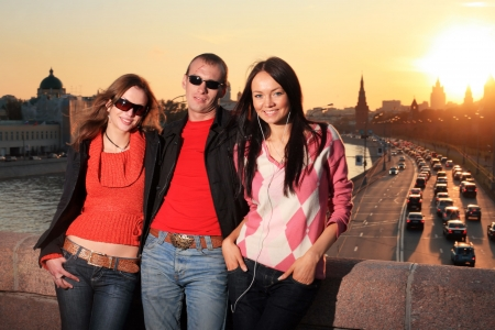 buckles: Man and two beautiful young women in Moscow city at sunset. Russia. Stock Photo