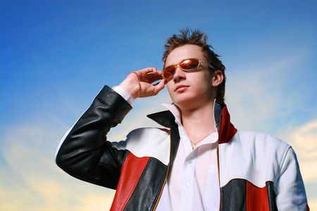 designer: Cool young man in sunglasses over sunset sky Stock Photo