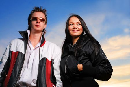 Cool looking young couple over dramatic sunset sky photo
