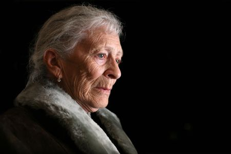 aging face: Portrait of a senior woman contemplating. Isolated on black background.
