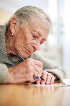 shallow dof: Portrait of a senior lady writing. Close-up, shallow DOF. Stock Photo