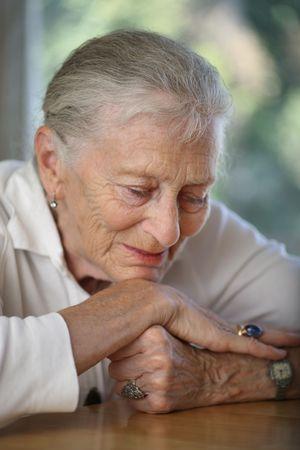 Close-up portrait of senior woman contemplating. Shallow DOF. photo