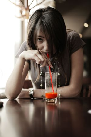 Brunette girl drinking red juice through straw. Shallow DOF.