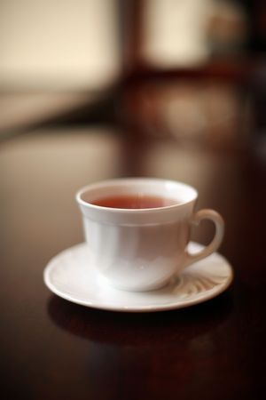 A white cup of tea on a glossy table. Shallow DOF.