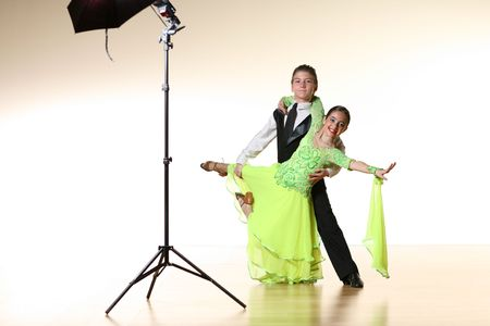 photoshoot: Boy and girl isolated over white wall posing for photoshoot in ballroom dance studio Stock Photo