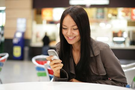Beautiful young woman smiling looking at mobile phone. Shallow DOF. Stock Photo