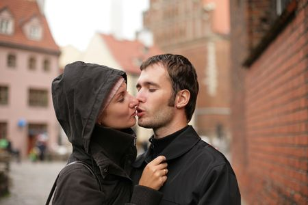 Young couple kissing in an old european town square. Stock Photo - 2475807
