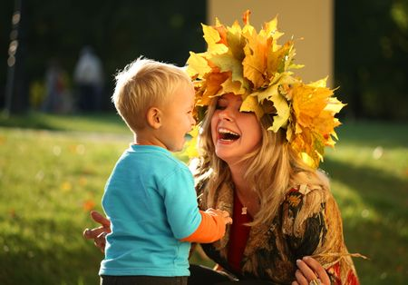 Young beautiful mother playing with her little son in an autumn park. Stock Photo