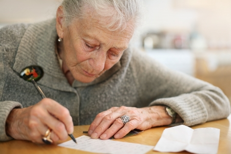 Portrait of a senior lady writing. Close-up, shallow DOF. photo