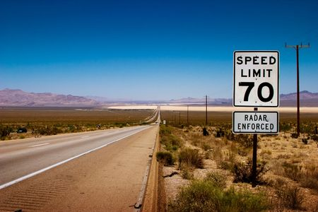 one lane street sign: Desert highway to horizon with a speed limit sign on a side. Stock Photo