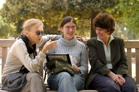 three generations: Grandmother and her doughter and granddoughter talking outside