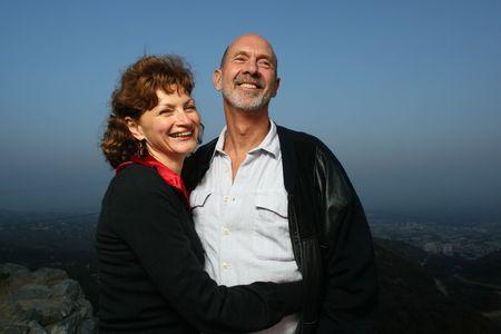pareja madura feliz: Feliz pareja madura ontop abrazando al aire libre de una ciudad.  Foto de archivo