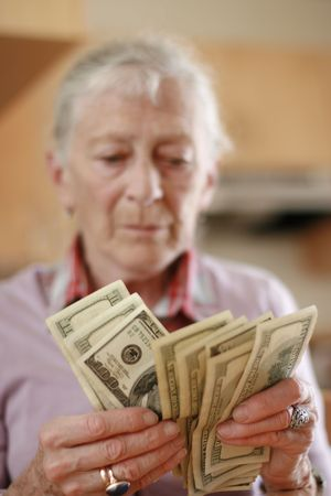 Senior woman counting savings money. Shallow DOF, focus on hands. Stock Photo - 2483245