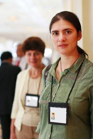 expositor: Dos mujeres de negocios en feria con el nombre insignias.