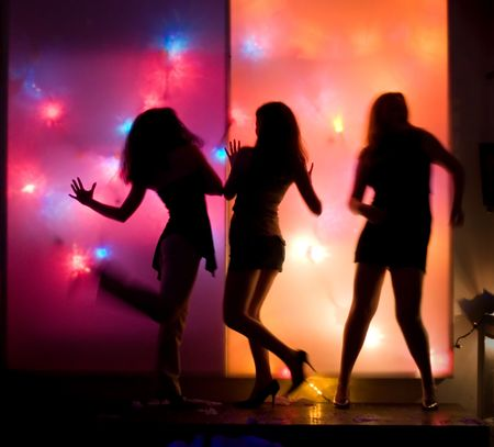 disco lights: Dancing girls silhouettes in front of colorful disco lights Stock Photo