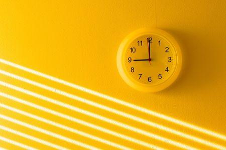 clock: Yellow wall & clock Stock Photo