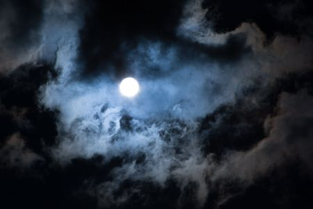 Sun shining through dramatic clouds, looks like a Moon. photo